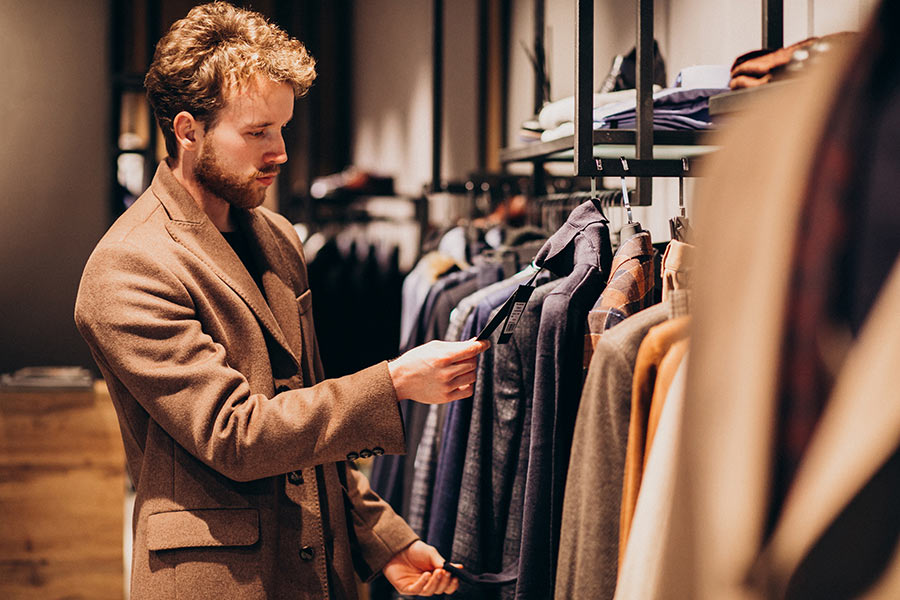 Young Handsome Man Choosing Clothes Shop